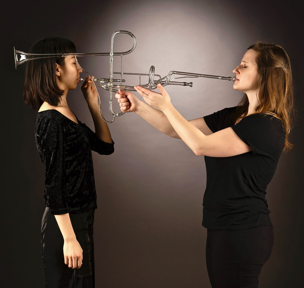 two women playing a glass trumpet