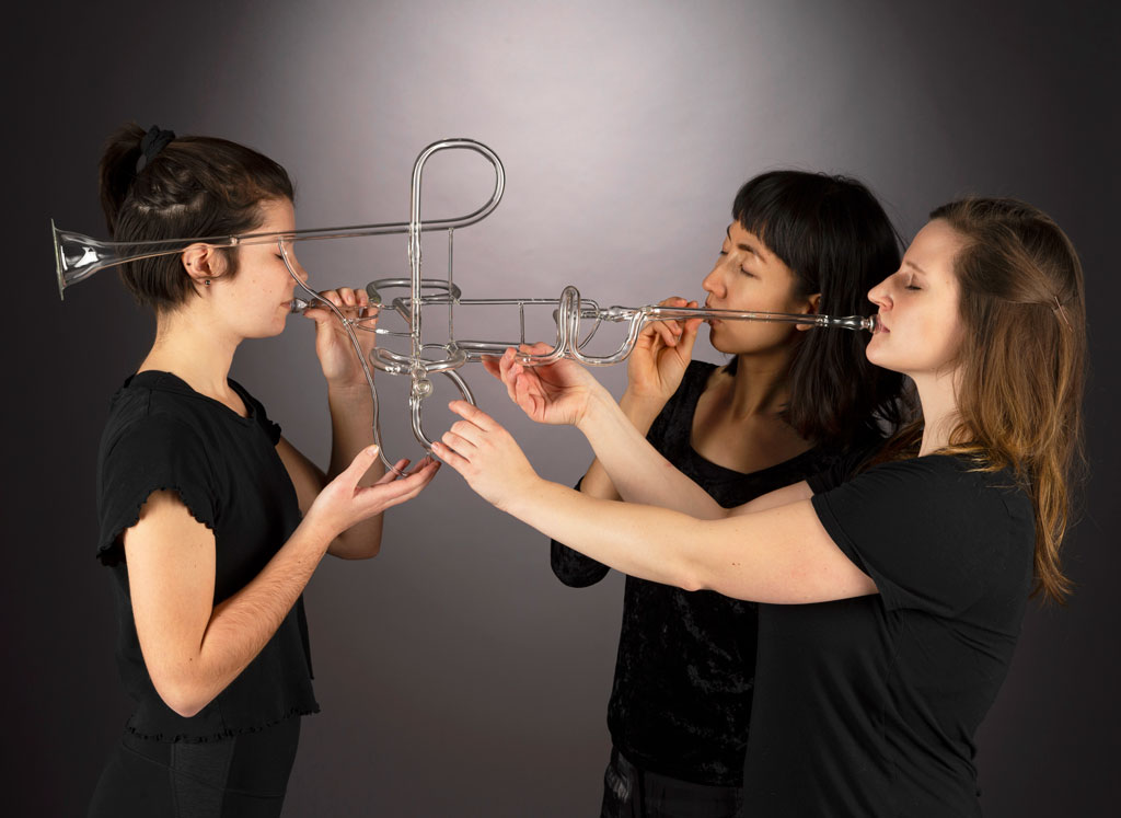 three women blowing a shared glass trumpet