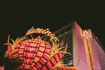 "a casino at night with the word ""flamingo"" in neon lights"