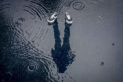 A pair of sneakers with a mysterious shadow, in the rain