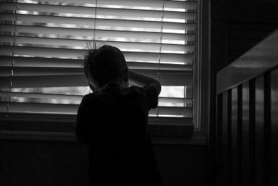 small boy peeking through a window to the outdoors