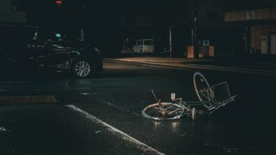 a bicycle lying in the roadway at night in the rain