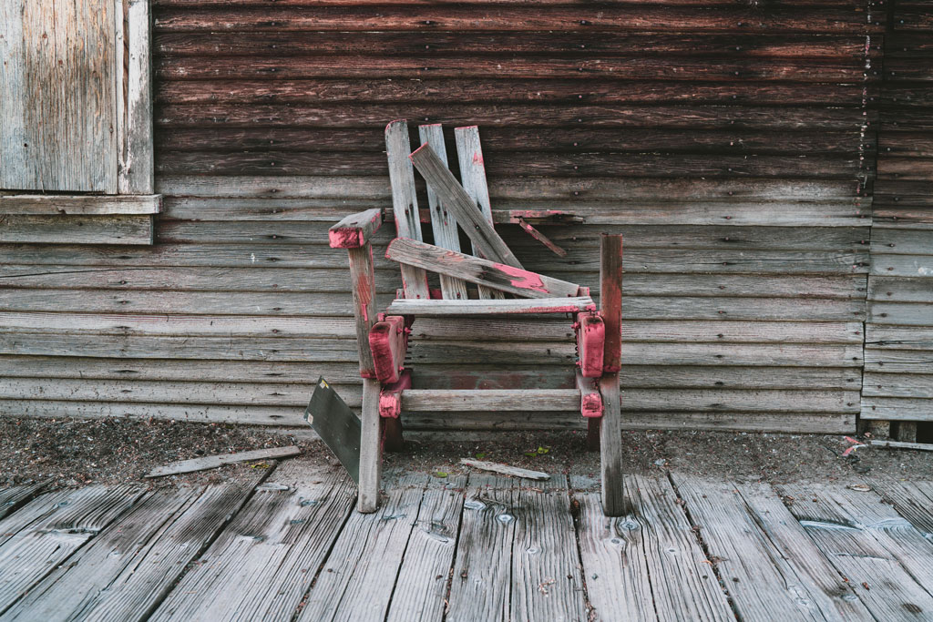 an old chair on a rotting porch