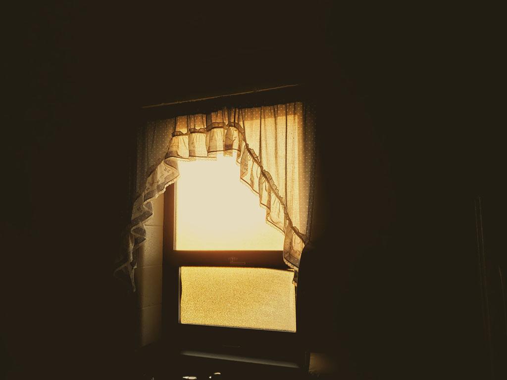 A dark room with a bright window