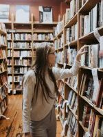 A woman browsing the fiction section of a bookstore