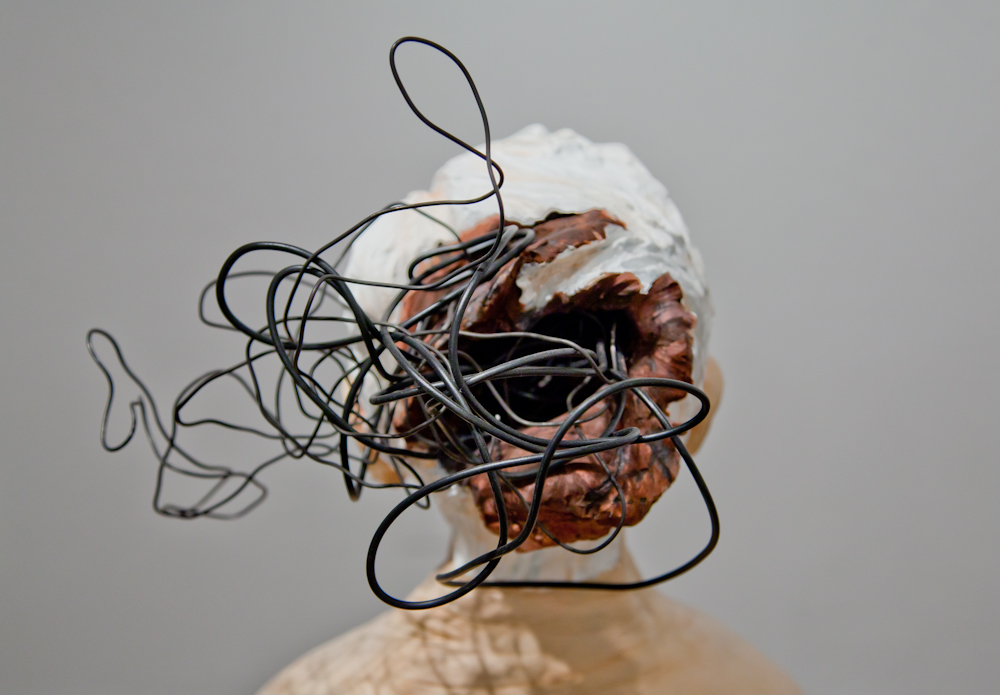 Back of the sculpted woman's head with black wires pouring out of open wound