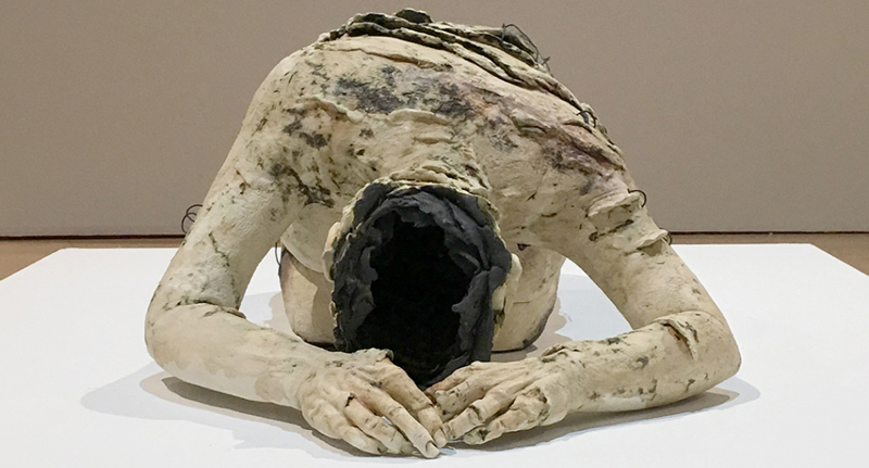 Front view of sculpted body with large black wound on head
