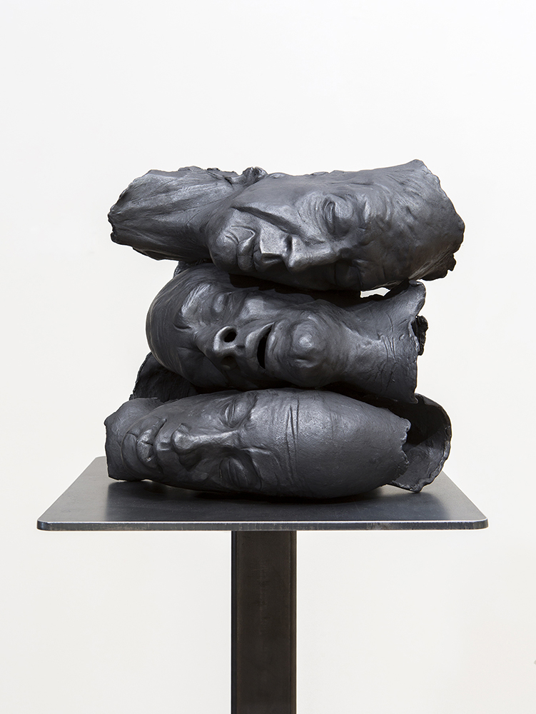 Three faces made of clay stacked on each other horizontally